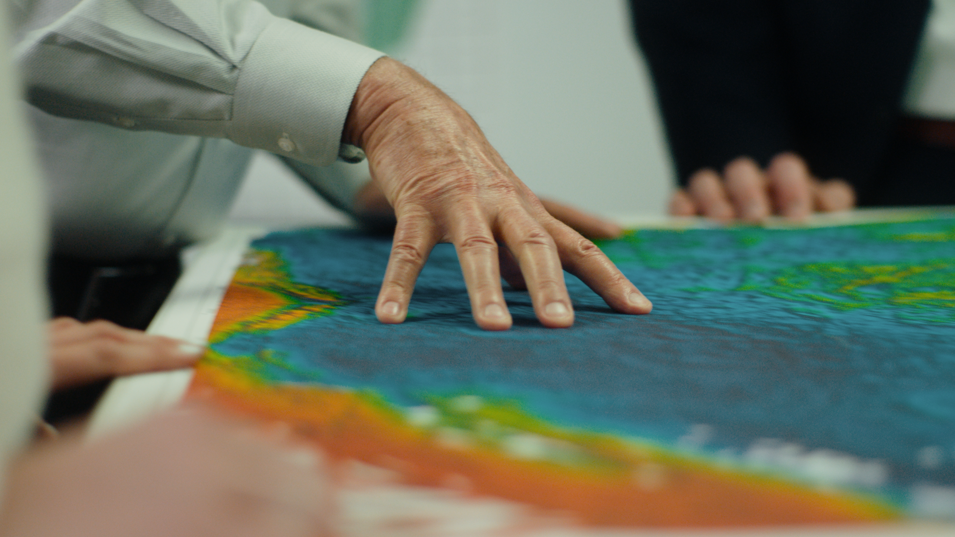 fingers pointing to plots on a map