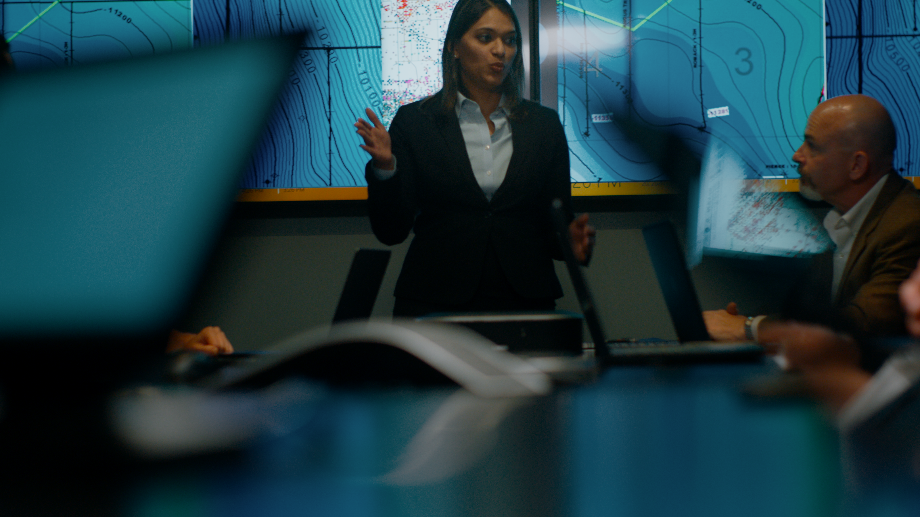 Female leading a group meeting with maps on screen
