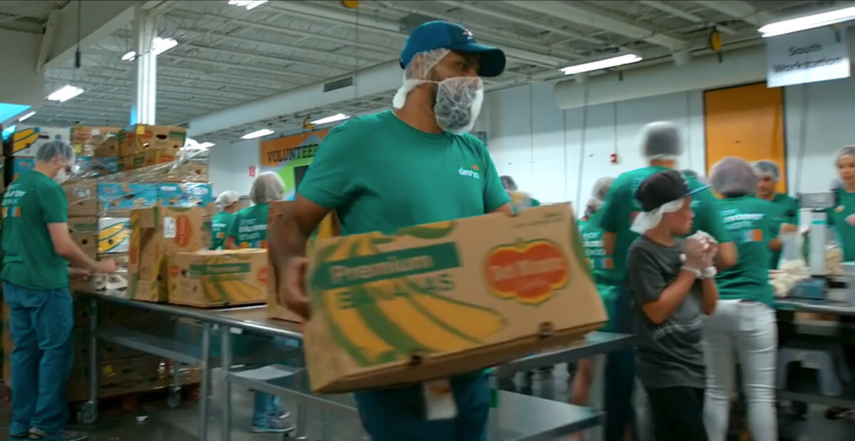 Regional food bank volunteer carrying a box of bananas while other volunteers help pack boxes.